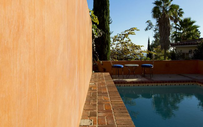 Pool with brick border and stucco wall